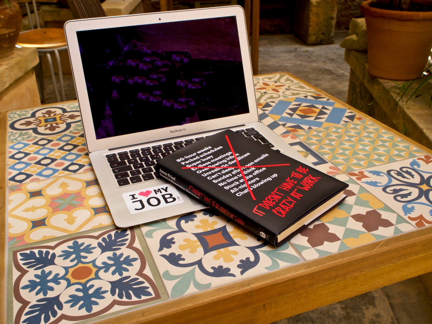 """Buch """"It doesn't have to be crazy at work"""" auf Laptop"""